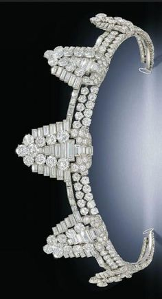Art Deco diamond tiara by Cartier. Composed of five graduated shield shaped clips, each tapered brilliant and baguette-cut diamond panel raised on the similarly-set diamond frame, circa 1930, with five detachable clip fittings, one brooch fitting and a cuff bangle, one diamond deficient. This tiara formerly belonging to Maureen Ward, Countess of Dudley, nee actress Maureen Swanson.