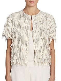 "Brunello Cucinelli Silk Fringe Bolero . Intricate laser-cut construction creates a voluminous layered fringe throughout this airy silk bolero. •Allover laser-cut fringe •Round neckline •Hook-and-eye front closure •Short sleeves •Lined •About 19"" from shoulder to hem •Silk •Dry clean . VANILLA"