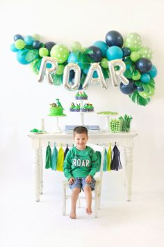 "Welcome to the dinosaur jungle! Children's birthday party inspiration. Dessert table decor. Blue and green balloons. Tassel garland. Little boy in ""roar"" party sweatshirt. T-Rex/Dinosaur Party styling by Happy Wish Company. Photography by Tammy Hughes Photography. Stationery by Minted artist, Patricia Wallace."