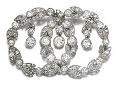 DIAMOND BROOCH, CIRCA 1910 Designed as a pair of interlocking wreaths millegrain-set with circular-, single- and rose-cut diamonds, suspending to the centre three similarly set articulated drops.
