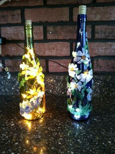 Wine bottles lit up with lights and decorated with sea glass finds!