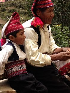 Taquile Island - A photo of grandfather and grandson.  The grandfather wears a hat that is all red – that signifies that he is married.  The grandson wears a hat that is red and white – that signifies that he is single.  A couple that is considering getting married lives together for two years before they wed.  On Taquile island there is no such thing as divorce.