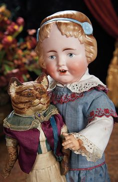 German Paper Mache Cat with Glass Eyes and Original Costume. Lot # 262.       Rare German Bisque Character Girl Model 1358, by Alt, Beck and Gottschalk. Lot # 263.