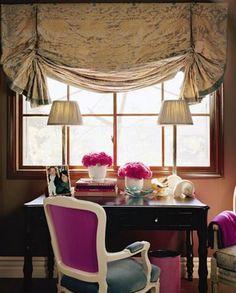 Cocoa brown walls, fuschia and grey velvet upholstered chair, two lamps, fuschia flowers - Joe Nye