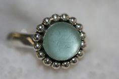 This ring is made entirely of 925 sterling silver.The ring have bezel mounting wher I set a 10mm rare genuine AQUA Blue sea glass piece. This