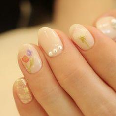 まるで水彩画のような愛らしいフラワーネイル。薬指には寄り添う新郎・新婦、人差し指には花嫁さんをイメージしたお花が描かれています。