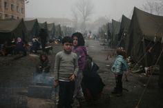 Refugiados sirios intentan mantenerse calientes cerca de una chimenea en frente de sus tiendas sin calefacción, en un campo de refugiados en...