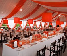 Colin Cowie Weddings - Coral and white organza fabric drapes from the ceiling of the tent. Coral lanterns hang above long dining tables.