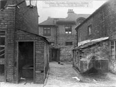 SEV/10/10 Black and white photograph of College Street, St.Helens.c1930s Court No. 2, Crab Street, St.Helens can be seen. Image shows rear of premises, yards and entry, and outside lavatory and water tap in the yard. Photograph relates to 1936 Clearance Order.SEV - St.Helens Metropolitan Borough Council, Environmental Health Section 10 - Photographs from St.Helens Borough Council, Health, Planning and Sanitary Departments.