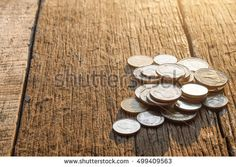 Thai baht coins. Coins on wooden texture under morning sunlight.