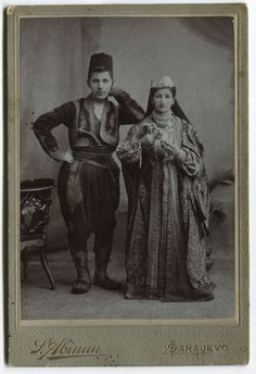 Studio portrait of a woman and a man, © The Historical Archive of Sarajevo. 1900-1915. Full-length shot of a man wearing an embroidered Bey's costume, a felt hat (fez). He is carrying a gun in his belt. His arm is resting on the woman´s shoulder. While pouring coffee, she is wearing a richly embroidered coat (anterija), dukats as a necklace and a cap.