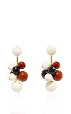 These earrings by **Marni** are rendered in resin and brass and feature multiple suspended acrylic spheres.
