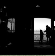 Silouhette of a man & a boy on the ferry in NYC., New York City, NY, USA