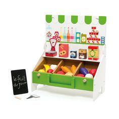 Avec cette épicerie, l'enfant joue à la marchande. Il installe les 8 fruits et légumes à découper en bois, les boîtes en carton et la balance. Il inscrit les prix sur l'ardoise et les étiquettes en carton. Ses clients repartent heureux, leur sac à provision en tissu rempli de bons produits. Cette épicerie est pliable et facilement transportable. En se transformant en petit marchand, l'enfant développe sa confiance en lui et son imagination.