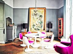 Colorful eclectic Mexico City interior with large painting and midcentury Saarinen-inspired fuchsia tulip table and chairs.
