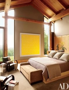 The master bedroom features a Larry Poons work titled Aqua Regia, Chinese Art Deco armchairs from TAMA Studios, a pair of silvered-Douglas-fir end tables from Design Within Reach | archdigest.com