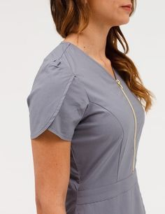 The Tulip Top in Graphite is a contemporary addition to women's medical scrub outfits. Shop Jaanuu for scrubs, lab coats and other medical apparel. Spa Uniform, Uniform Ideas, Scrubs Pattern, Stylish Scrubs, Scrubs Outfit, Medical Uniforms, Medical Scrubs, Nursing Clothes, Graphite