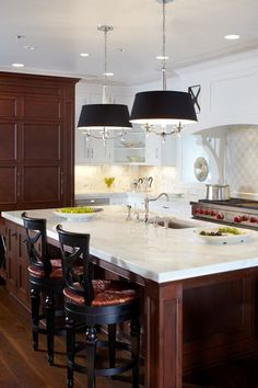 This luxurious white kitchen mingles exquisite furniture-grade cabinetry with hand-painted details and artisan-crafted metal work. A spacious island provides plenty of prep space.