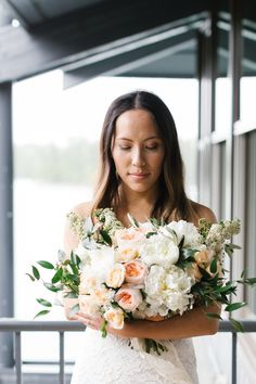 This bridal bouquet is full of white peonies, Juliet garden roses, peach spray roses and spirea! A perfect June bridal bouquet! Photo: Shannon Yau Photography Bouquet: Flowers by  Janie Calgary Planning: Paper Doll Events