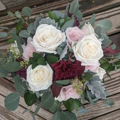 With burgundy dahlias, leucadendron, ivory and dusty rose roses, and dusty miller and eucalyptus greenery.