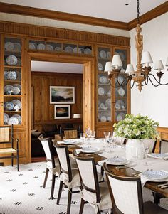 The designer created a warm feel in the breakfast room with built-in cabinets of reclaimed antique white pine. A simple Louis XIV chandelier lends the room a low-wattage opulence, and the client's collection of English blue-and-white china (extravagantly mismatched) gives the room a homey sense of elegance and fun. 1940s Belgian chairs upholstered in linen from Hinson surround an Italian Renaissance-style oak refectory table.   - HouseBeautiful.com