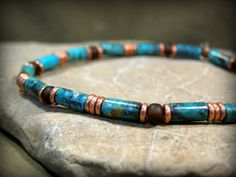 A classic style bracelet beaded with stabilized turquoise 9x4mm tube beads with African copper heishi and matte dark topaz 6/0 seed beads as