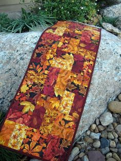 This is a very colorful table runner to place on your table. The colors consist of the beautiful hues of autumn. There is mainly red, gold, rust and orange in this runner. The fabrics are full of leaves. The backing has a black background with a mixture of fall leaves. This runner would look great on a coffee table, buffet, dining room table, kitchen table or wherever you like. This runner is 12 wide by 36 in length. The fabric and batting are 100% cotton. The batting used was Warm and…