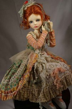 A repin of a red-haired doll dressed in greenish gray and muted coral #doll