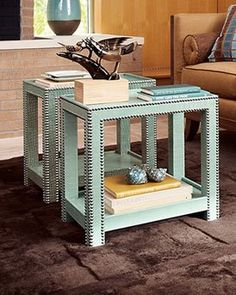 This would be an inexpensive DIY project. Get a couple of unfinished pine tables, spray paint them, and then stick thumb tacks in it to mimic the nail head finish. Finally, buy a few pieces of plexi glass for the topper