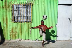 A young boy playing soccer in the township. It is a sport also very popular in South Africa. Kids Soccer, Cape Town, Cinematography, South Africa, Planets, Backdrops, African, The Incredibles, Tours