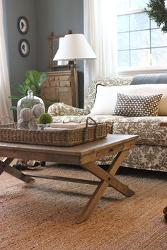 Love the sisal rug with the traditional fabric on the setee and the classic silhouettes. The single basket on the coffee table that houses the other things gives a unified non cluttered feel.