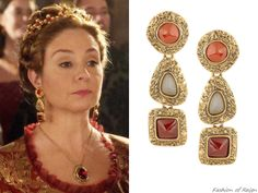 "the CW's Reign Fashion & Style In the episode 2x05 (""Blood for Blood"") Queen Catherine wears these sold out Oscar de la Renta Tiered Gold-Tone Clip Earrings.  Worn with a Paris by Debra Moreland headpiece."