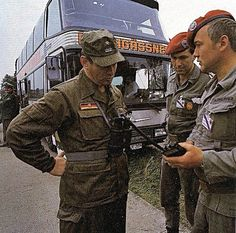 East German soldier with two West German soldiers at the end of the cold war