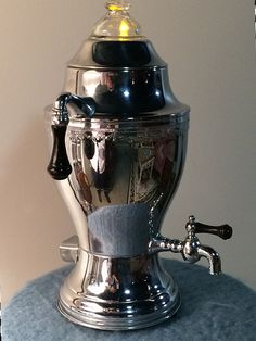 Vintage Coffee Pot Percolator. This Art Deco electric coffee pot has a silver finish decorated with and laurel garland etched around the top with classic black knob handles and a simple tea light that illuminates the Glass Percolator Lid. We had thought of using an electric light,