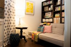 couch in front of the book shelves -- pretty things on top, storage on bottom out of sight