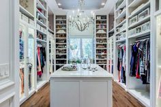 Stunning walk-in closet boasts an antiqued mirrored closet island with clear top fitted with jewelry drawers placed in front of wall with floor to ceiling shoe shelves with custom lighting. New Homes, Shoe Shelves, Master Bedroom Closet, Closet Vanity, Closet Designs, Home, Interior, Closet Bedroom