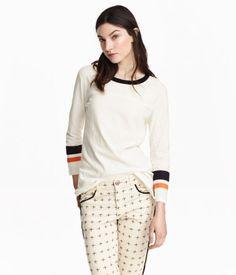 Shirt aus genopptem Jersey. Das Shirt hat eine Kontrastblende am Ausschnitt, 3/4-lange Ärmel mit Druck und seitliche Schlitze am Saum.