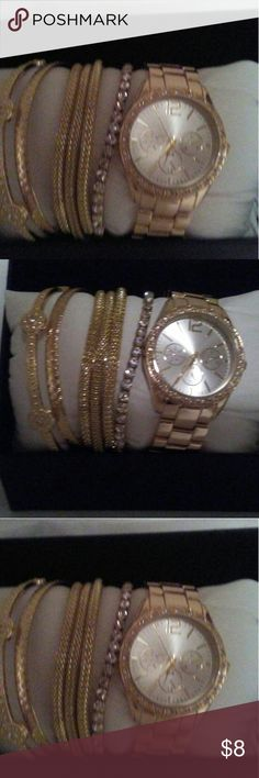 A watch with a gold tone face. And crystals. Arou. Gold tone band with sliver. face and crystals around the edge and comes with 6 bracelets. Jewelry