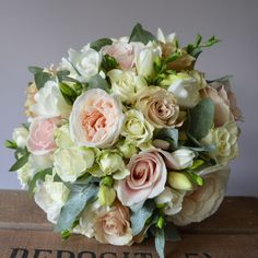 Neat hand tied bridal bouquet of soft pinks and nudes created by Eden Blooms Florist for Farnham Castle bride. Made from Cream Spray Rose, Quicksand Rose, White o'hara Rose, Sweet Avalanche, Cream Freesia, Eucalyptus Cenerea.