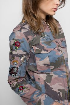 Zadig & Voltaire jacket, high neck, camouflage print, patch breast pockets and side pockets, zipper fastening, decorated with brightly-colored circus embroidery, 100% cotton. The circus motif, a colorful mix of dancing skeletons, flowers and animals, is the product of a collaboration with Brooklyn tattoo artist Virginia Elwood.
