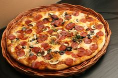 Italian pizza with pepperoni, black olives and mushrooms. Baked in an electric stone oven at 400 degrees celcius. With crust based on sourdough and fiordilatte cheese.