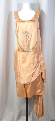 Exquisitely made mid-1920s peach silk satin evening dress features a bodice beaded with clear rhinestone pastes in a Deco design and, over the left back hip, a dramatic swag and trailing panels. #vintage #deco #fashion