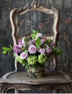 Chair, bark wrapped vase, lilac roses
