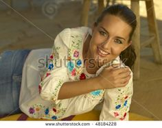 Native American brunette model wearing embroidered blouse laying on woven rug at Arizona ranch.