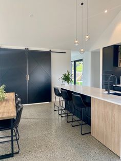 Black barn doors compliment the black in the kitchen of this luxury home in Jacks Point. Black Barn, Polished Concrete, Showcase Design, Concrete Floors, Hand Blown Glass, Barn Doors, Luxury Homes, House Plans, New Homes