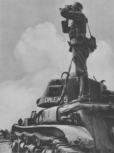 """German Soldier scanning the horizon from atop a knocked-out French Hotchkiss H35 Light Tank, nicknamed ,,Orléans""""."""