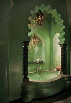 Dark & dreamy bath, this exotic green bathroom design is reminiscent of a Turkish style bathhouse. Pillars, an archway entrance & hanging lanterns add a special touch.
