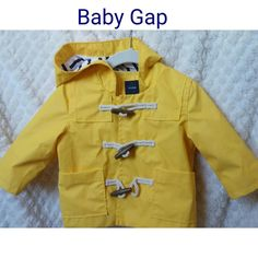 NWT BABYGAP slicker Baby Gap yellow soft slicker Rain Coat  wood and toggle closure over snaps  soft yellow cotton lines body  Stripped navy/white cotton line hood  new never worn  bright yet soft yellow color   size 6-12months but can easily be worn past 12months for awhile. Gap runs big GAP Jackets & Coats