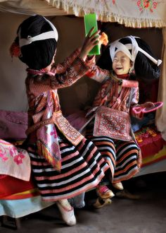 quickwitter:  theworldwelivein:  Changjiao Miao girls playing with mirrors, Longga, China © Kieron Nelson