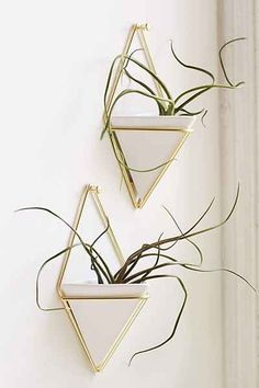 "Umbra Trigg Wall Planter Set $30 Hanging wall planters designed by Moe Takemura for Umbra. Metal wire frame with ceramic diamond-shaped drop for holding anything from plants to pens. Set of 2.  Content + Care - Set of 2 - Ceramic, metal - Wipe clean - Made in the USA  Size - Length: 4.5"" - Width: 2.75"" - Height: 7.25"""